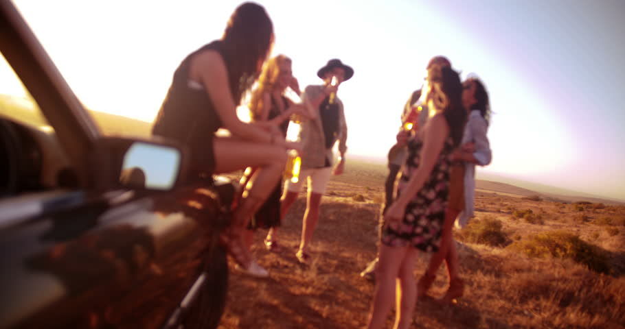 Group of friends toasting with beer outdoor on a summer sunset evening during their vintage convertible road trip | Shutterstock HD Video #15088429