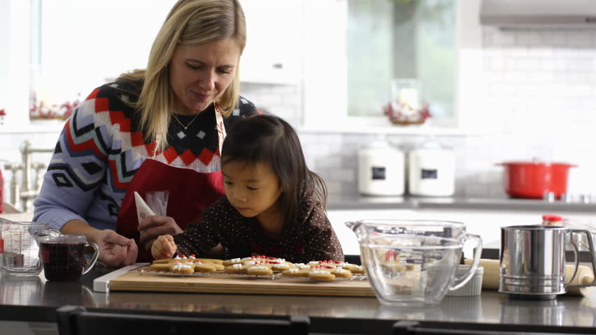 Mother and daughter frosting gingerbread cookies