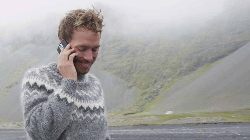 Phone man talking on smartphone walking on black sand beach on Iceland wearing Icelandic sweater by the ocean sea. Handsome Caucasian male model using smartphone. 60 FPS. | Shutterstock HD Video #15135364