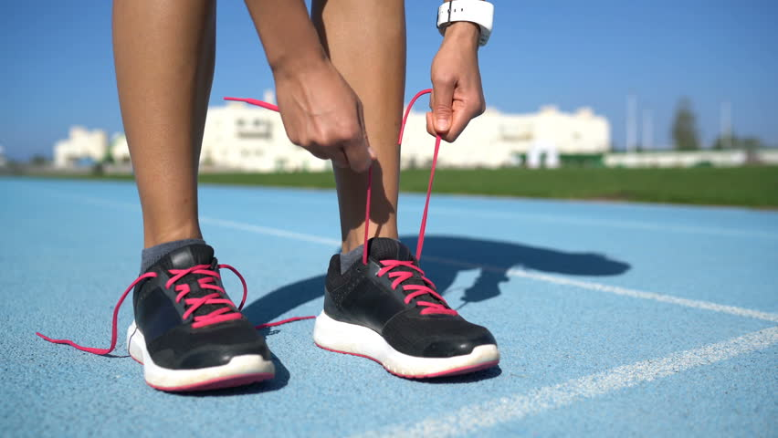 Runner woman tying the laces of her running shoes getting ready for race on run track. Female athlete preparing for cardio training .Closeup of feet and hands. #15166927