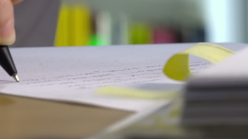 female hand hand writes on white paper sitting at the desk: working, studying - 4K stock video clip