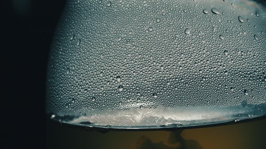 Tea making in a glass kettle. Drops, bubbles and steam. Macro shot. Canon 5d mark iii Magic lantern raw. - HD stock footage clip