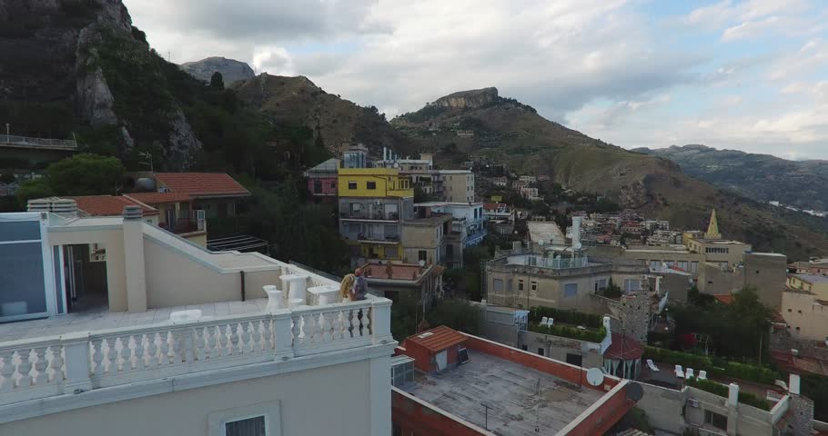 Aerial shot of a happy young couple on a terrace of a hotel with sea views - 4K stock footage clip
