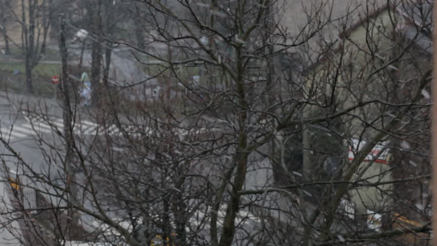 View from the window. Trees, houses, roofs, doroga.Idet snow, riding cars, people go. Blurry, without harshness. Boke. - HD stock footage clip
