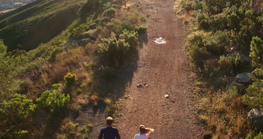 Multi-ethnic group of athletes running together on a panoramic nature trail. Aerial drone view.