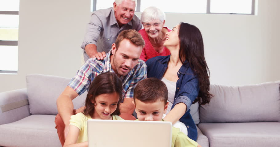 Smiling multi generation family using laptop in living room - 4K stock video clip