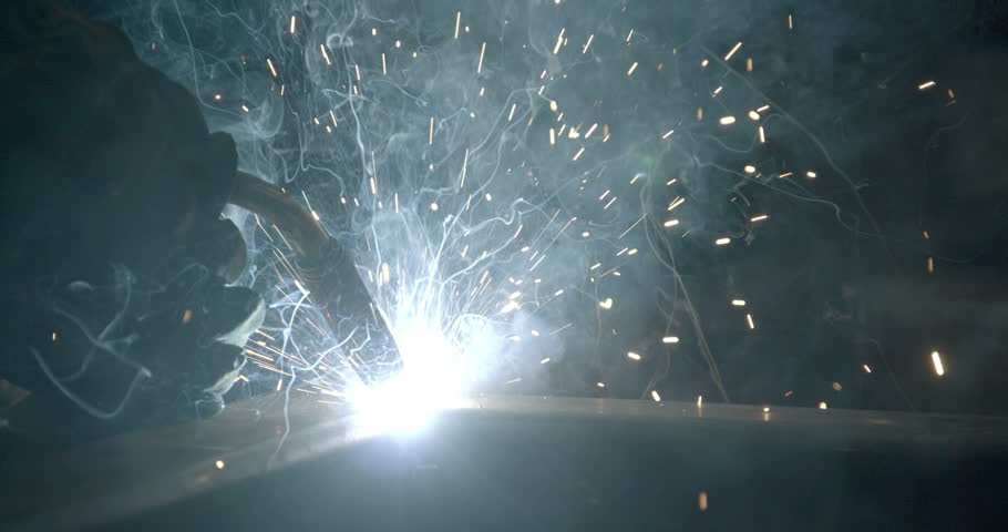 The light of the welding machine on the tip of the machine doing the works on the factory - HD stock footage clip