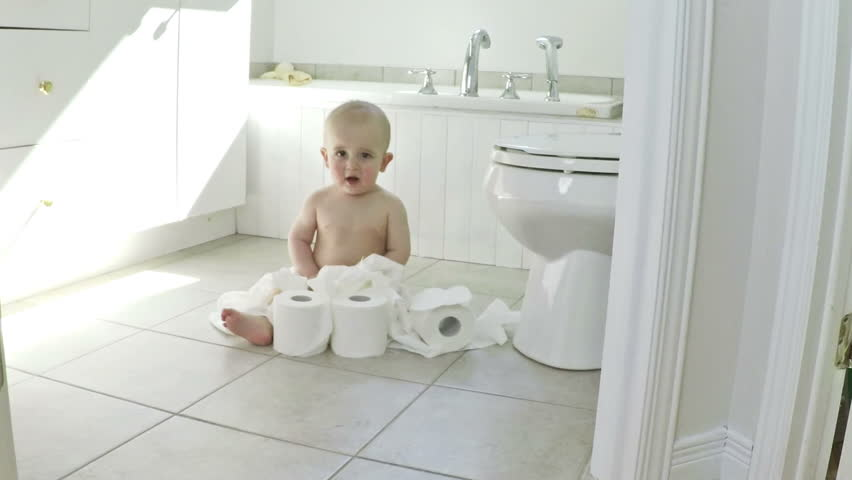 Adorable baby boy playing with toilet paper