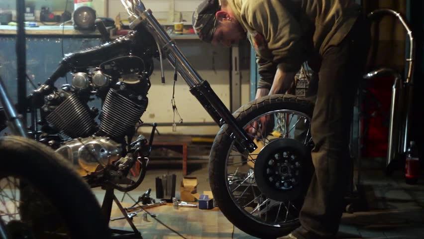 Auto mechanic assembles custom motorcycle in his workshop for Garage custom moto