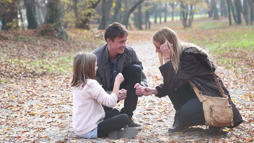 Attractive young parents having fun with cute daughter playing games in the park, slow motion - HD stock footage clip