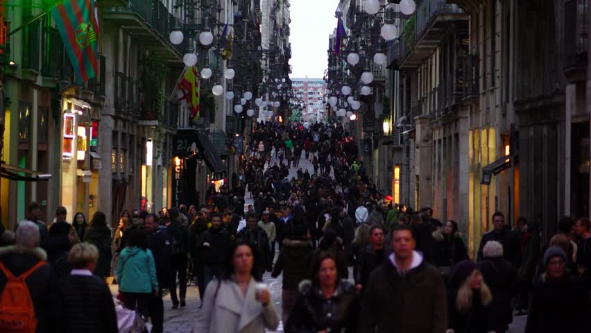 BARCELONA, SPAIN - FEBRUARY 28, 2016: Unidentified people crowd walk at Carrer Ferran, slow motion, twiligh time. Tourist and citizens come along alley towards and from Rambla dels Caputxins