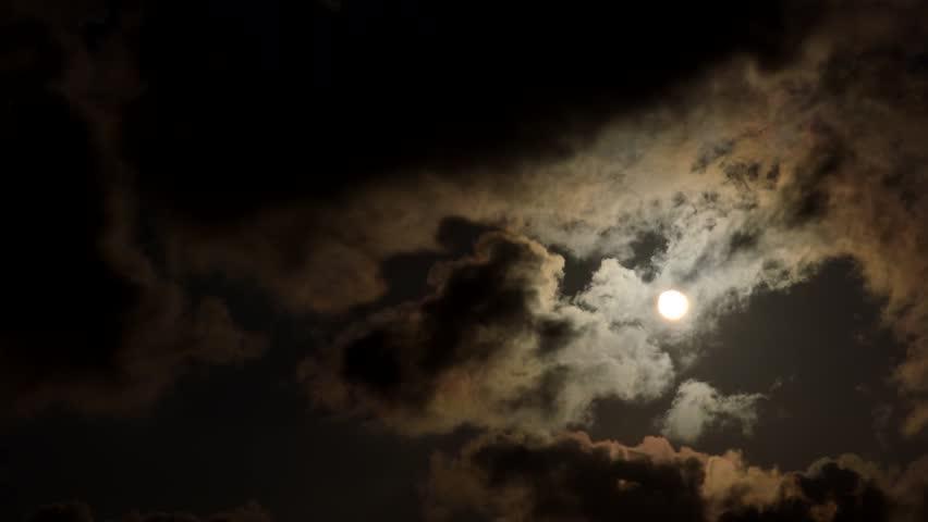 Sun movement through dark ominous clouds. - HD stock footage clip