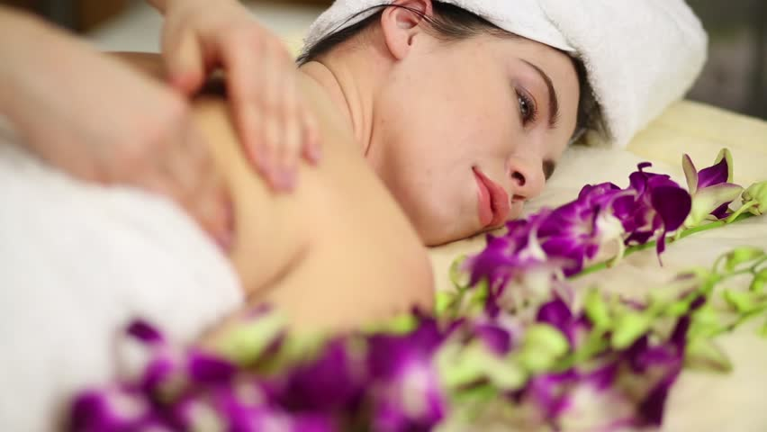 Woman on bed among orchids doing shoulder and back massage at beauty salon. | Shutterstock HD Video #15534739