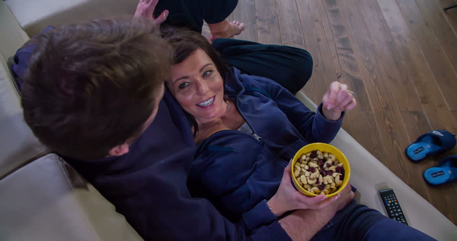 A woman is feeding her husband with some nuts when they're watching TV. They're sitting on a couch in the living room. Their slippers are on the floor.    Shutterstock HD Video #15536017