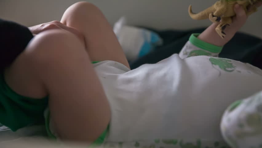 A boy is lying on a bed and his mom is putting him green pants on because she just changed him a diaper. Close-up shot. - HD stock footage clip