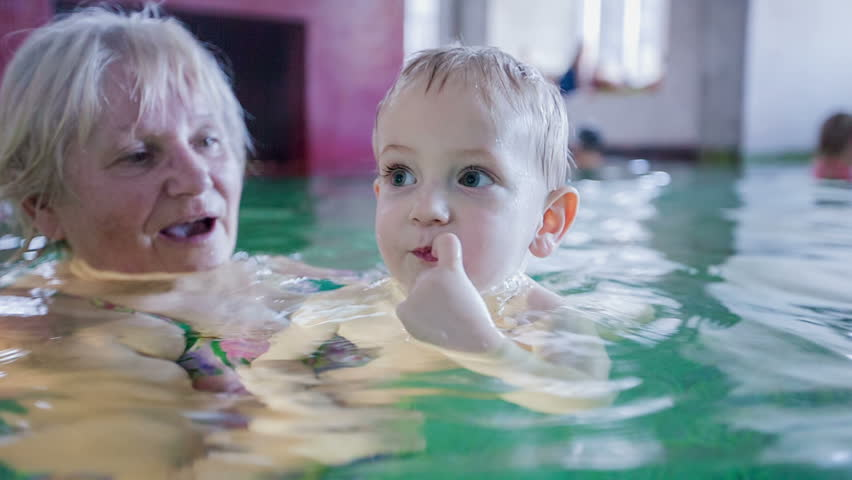 Grandma is holding her grandson in her arms in a swimming pool. He is showing something with his hands. Close-up shot.   Shutterstock HD Video #15539365