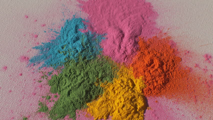 Colorful rainbow holi powder bounces off white canvas background in rainbow shockwave pattern, slow motion