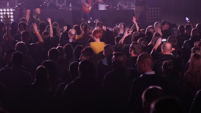 KHERSON, UKRAINE - MAR 26, 2016 - Free public music concert - Dancing cheering crowd fan spectators rais hands at concert lumiere spot lights - HD stock footage clip