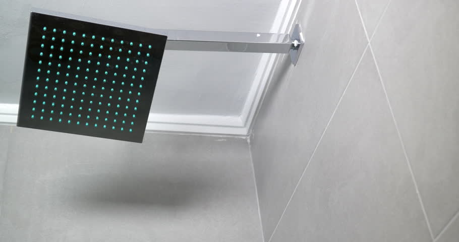 Hot water is streaming from the modern square shower head. Steam is appearing on the door of shower cabin. | Shutterstock HD Video #15637852