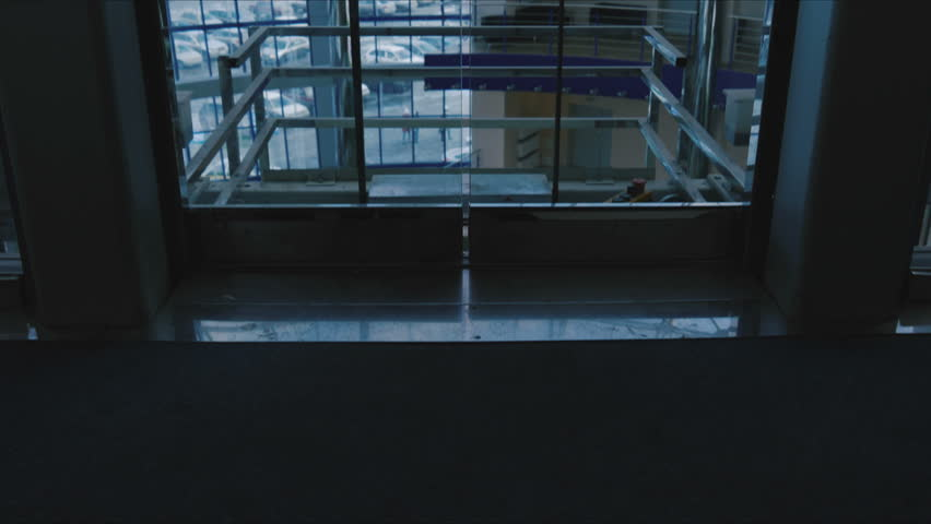 Two men emerge from the glass elevator - 4K stock video clip
