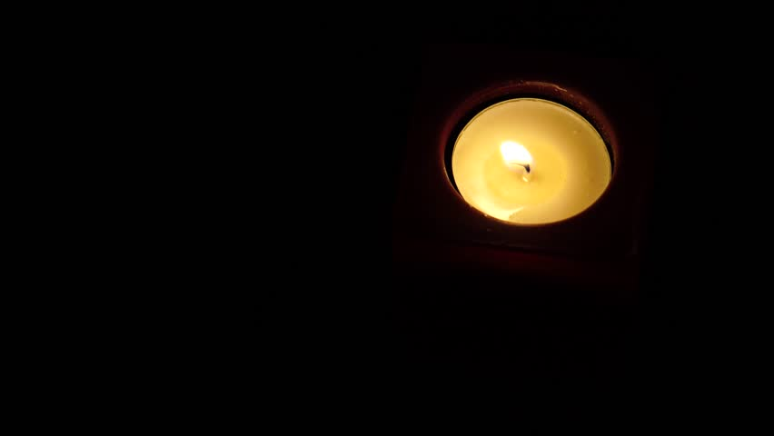 Top down shot of round tea light candle burning in the dark. Lot of copy space. - 4K stock footage clip