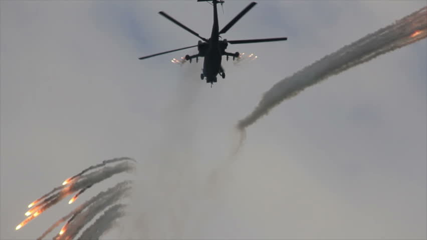 Military helicopter circling flight and shoots flares dodging gunfire