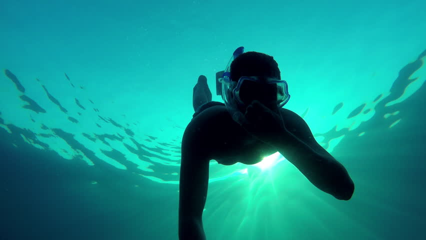 Young athletic diver underwater shot wildlife fish for Fish swimming backwards