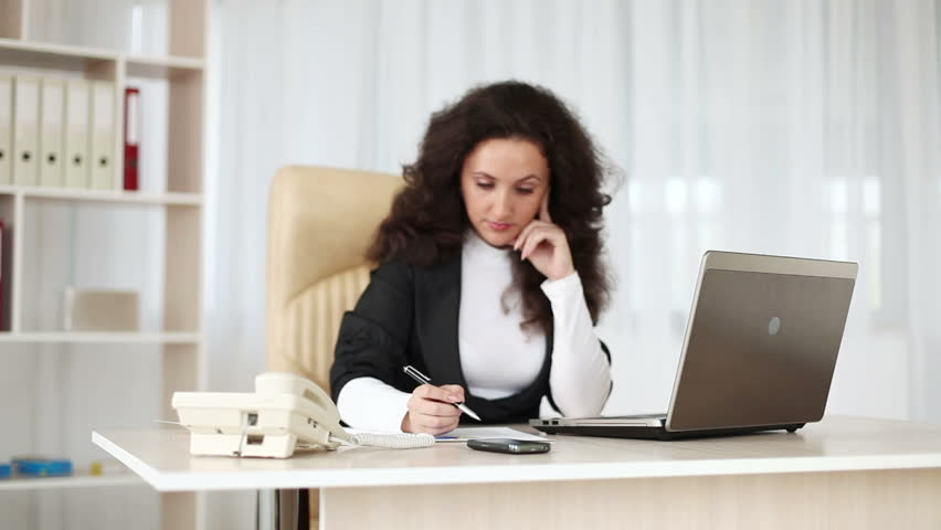 Asian Businesswoman Talking On Phone While Working At Desk