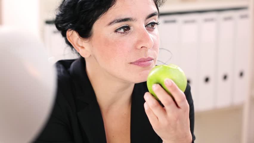 Healthy hispanic businesswoman eating apple - HD stock footage clip