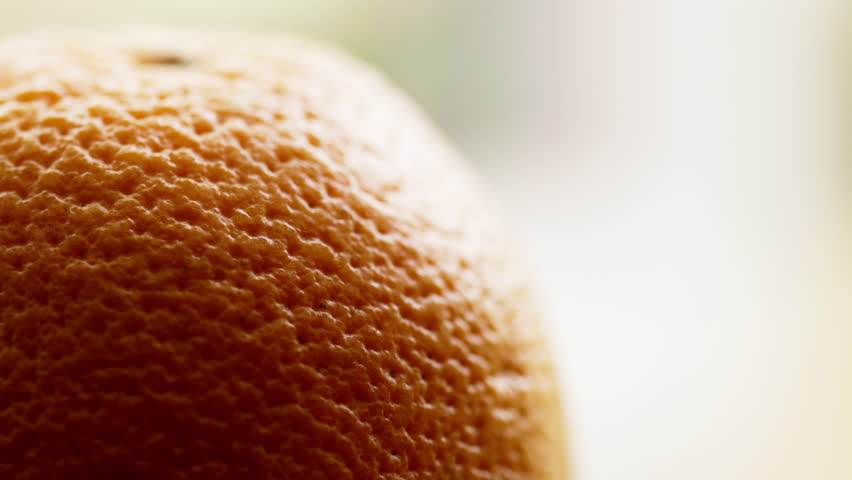 Orange in extreme close up UHD stock footage. An Orange in true macro close up with subtle lighting for an elegant effect. Rotational camera move and fine detail texture.