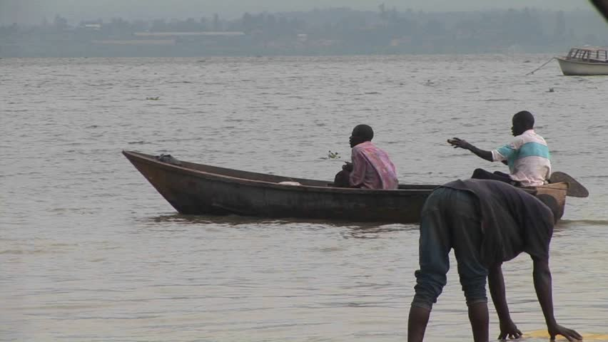 LAKE VICTORIA, UGANDA - CIRCA 2009: Man rows a jon boat amidst a group of other fishers circa 2009 in Lake Victoria. Uganda. - HD stock footage clip