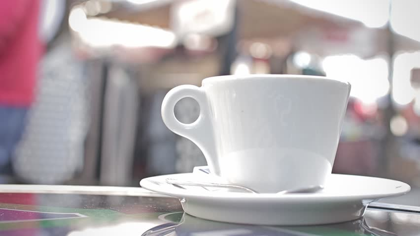 Hand Takes Coffee Mug To Drink In Terrace in Paris, France. Drinking coffee in a french restaurant terrace in Paris on a crowded street.   Shutterstock HD Video #15815170