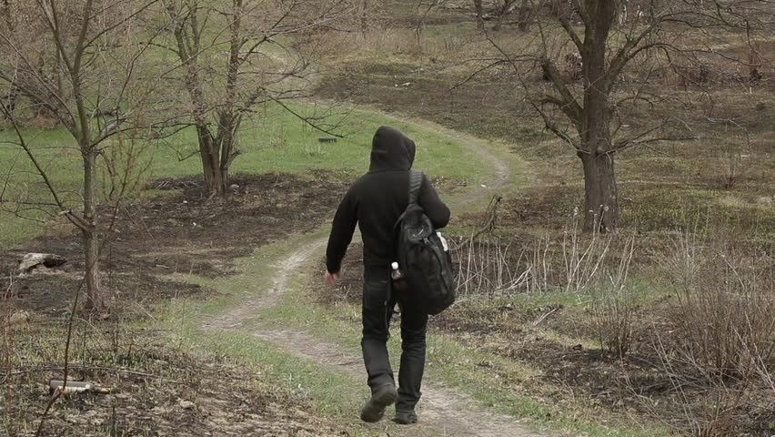Adult male with a backpack goes on the trail