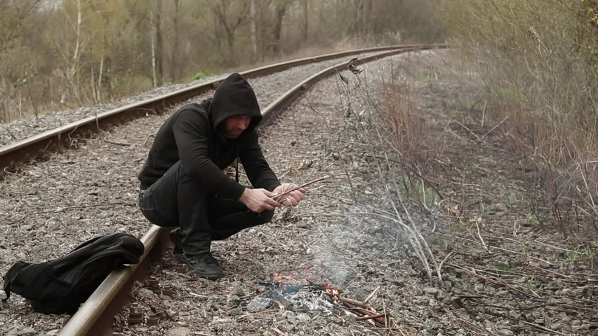 Man acting as a refugee on a railway