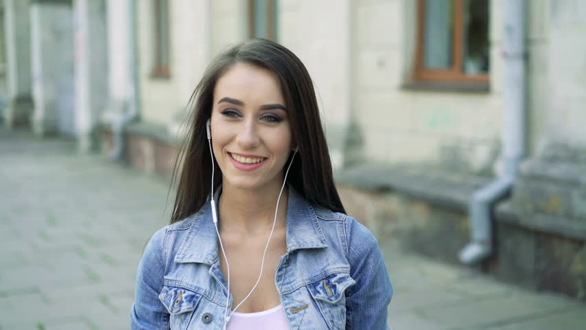 Girl listening music, boy coming to her, smiling on the street. 4k | Shutterstock HD Video #15827689