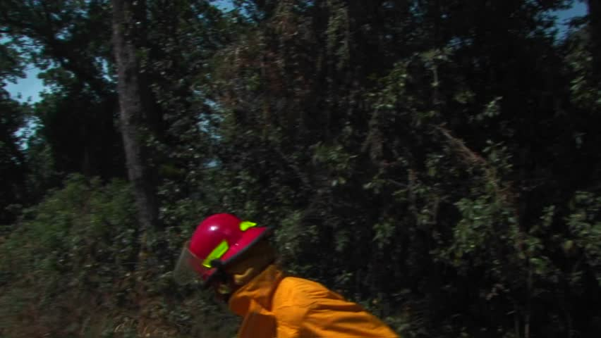 A firefighter walks quickly down a dirt road approaching a wildfire - HD stock footage clip