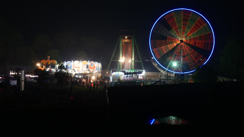 Ferris wheel and other rides at an amusement park at night - 4K stock video clip