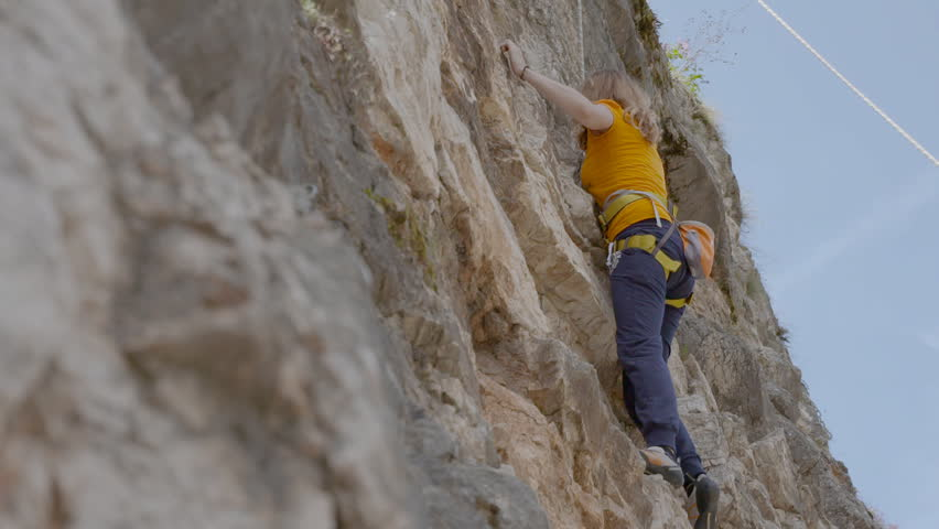 A female rock climber climbs up a rock. Learning to climb - HD stock video clip