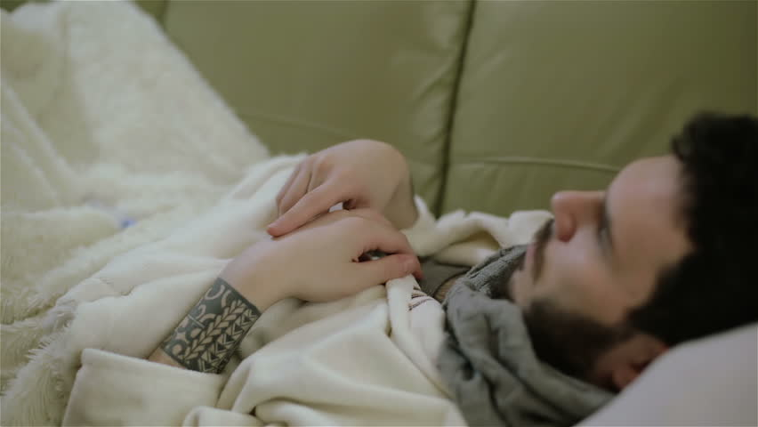 A black-haired tattooed man with a beard taking his temperature with an electronic thermometer. He lies on a sofa under a white blanket. He wears a gown and a scarf. | Shutterstock HD Video #15920902