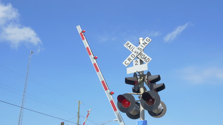SLOW MOTION CLOSE UP: Level railroad crossing with barriers lowering and red lights flashing announcing coming train on sunny day - 4K stock video clip