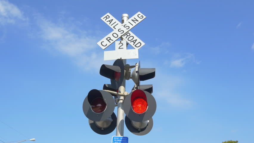 SLOW MOTION CLOSE UP: Level railroad crossing with barriers lowered and red lights flashing warning and announcing coming train on sunny day - 4K stock video clip
