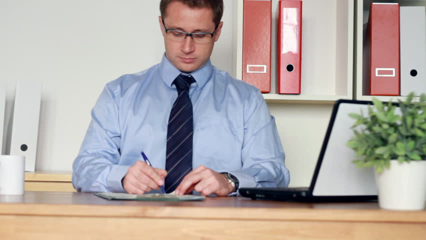 Happy businessman signing documents in the office, camera stabilizer shot - HD stock video clip