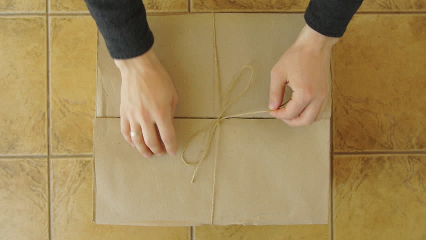A young man hands opens a parcel contains a gift. Unpacking box with another box. Surprise. People, delivery, shipping service, opening cardboard box or parcel at home.