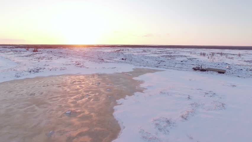 aerial sunset view of heavy truck driving on snow-covered winter road - 4K stock video clip