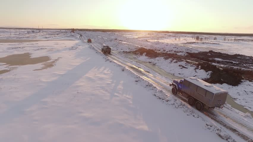 aerial sunset view of vehicles convoy driving on snow-covered winter road - 4K stock footage clip