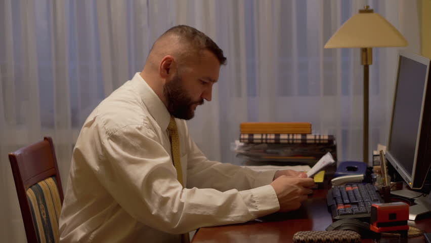 Angry businessman scatters documents on the desk at work in home office   - HD stock video clip