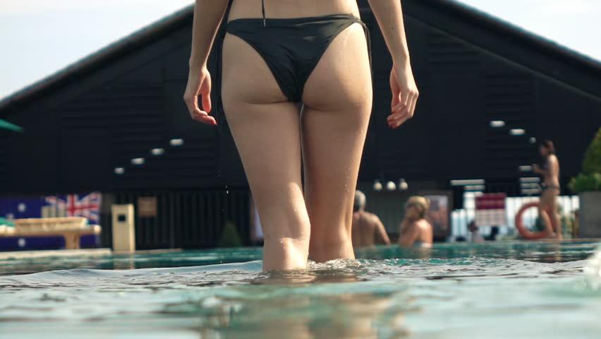 Sexy woman in bikini walking into swimming pool, super slow motion 240fps  - HD stock footage clip