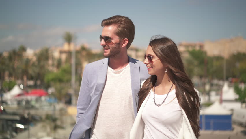 4k footage, hipster rich couple walking along marina on sunny day during their honeymoon