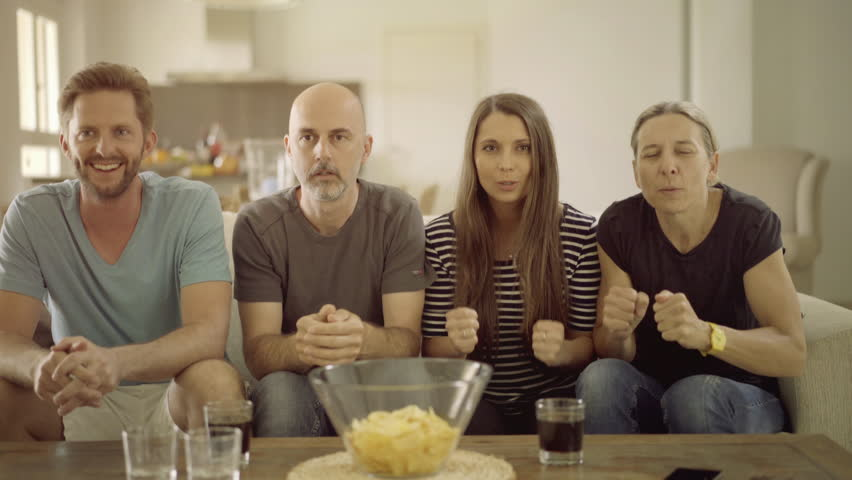 4k footage, four friends watching major sport event on tv at home, three cheering one annoyed