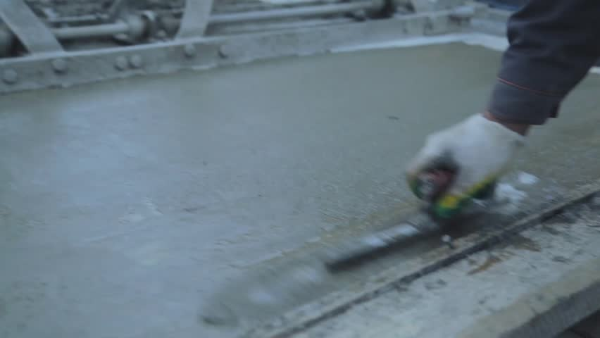 Concrete Worker Smoothing Wet Sidewalk. Pouring Concrete. A factory worker uses a shovel to level and smooth wet concrete on a floor in a factory or at the construction site. Slow motion shot. #16355971